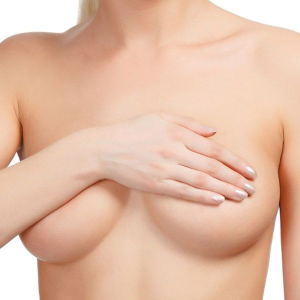 Woman holding hand over bare breasts