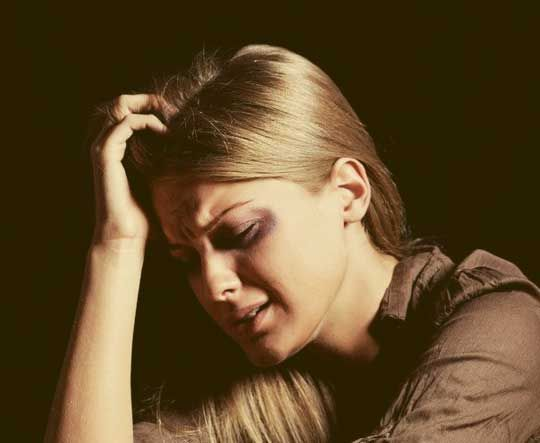 A blonde woman looking distraught in a dark room