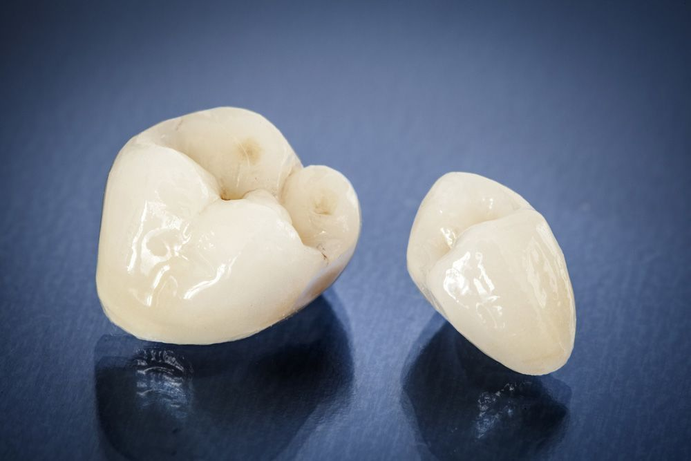 Two dental crowns against a dark background