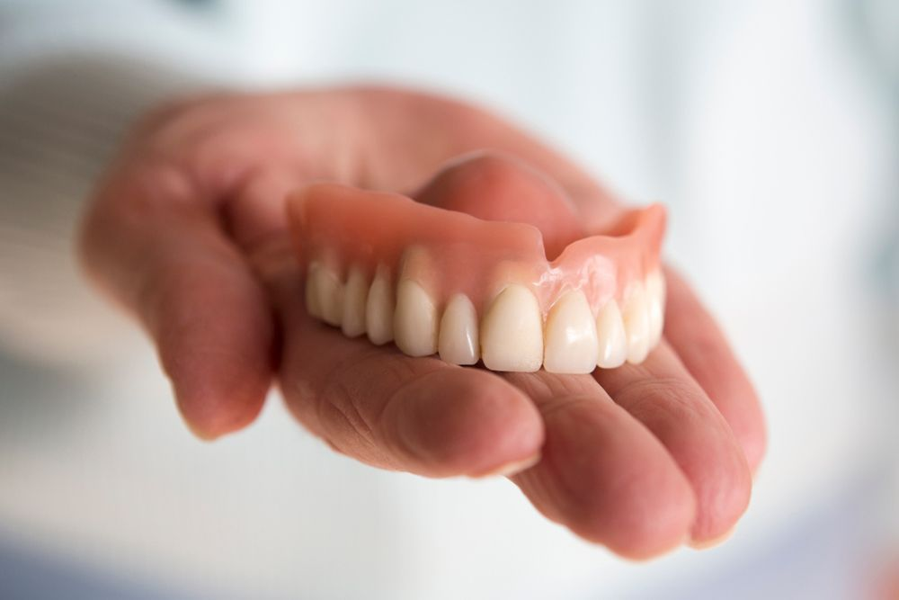 Photo of a hand holding a denture