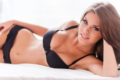 Woman lying on a bed in a black bra and panties.
