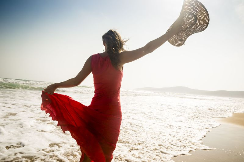 Woman in red dress on beach and holding hat in the air