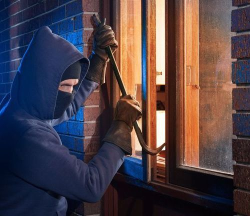 Masked man breaking into house