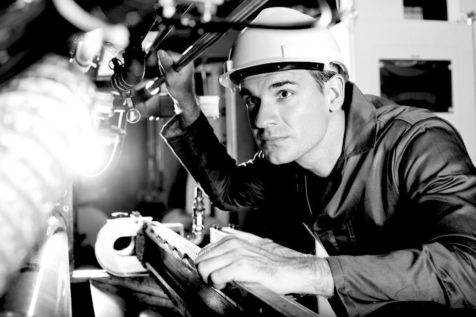 A worker with a hard hat examines machinery