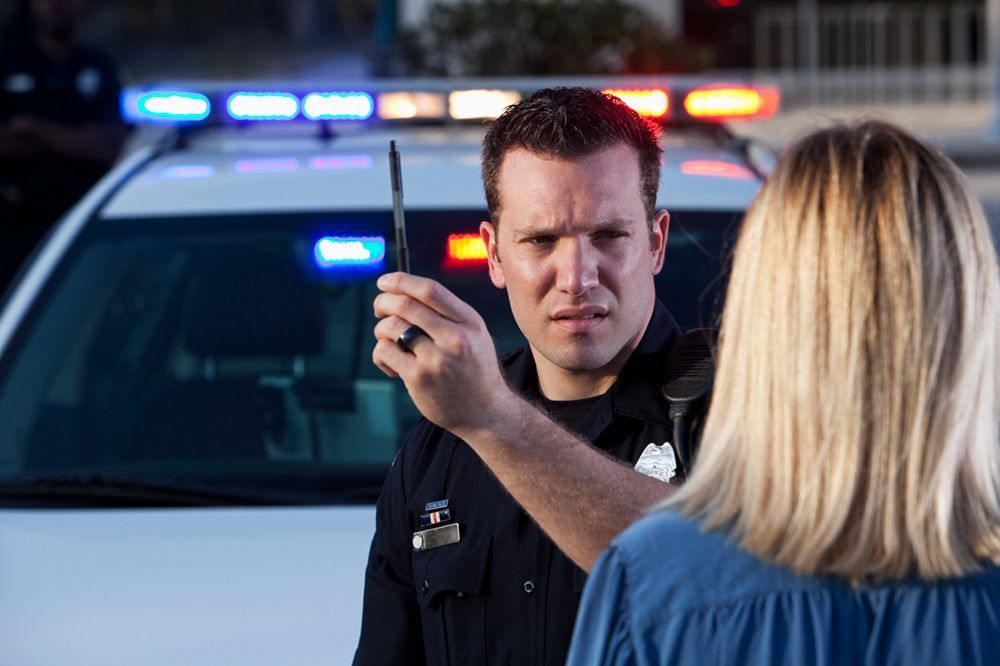 A police officer administers a roadside sobriety test.