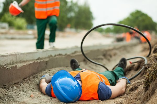 A man lies on the ground next to an electrical wire