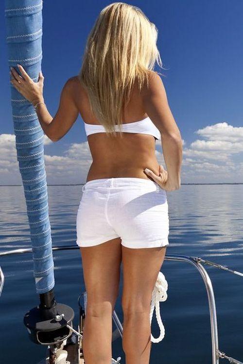 Woman on boat in white shorts and bikini top