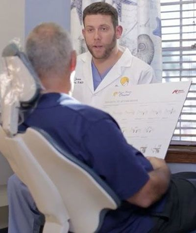Dentist speaking with patient holding brochure