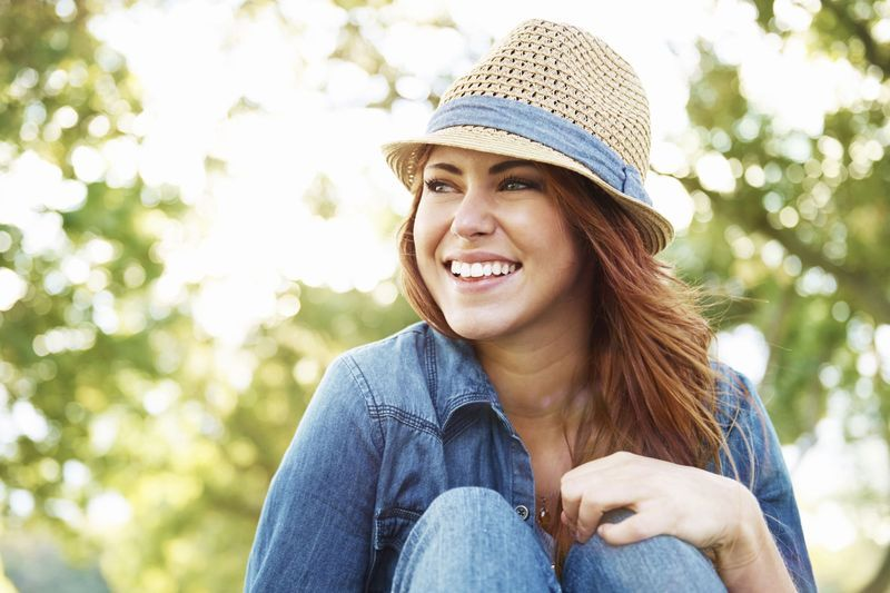 A smiling woman in a funny hat