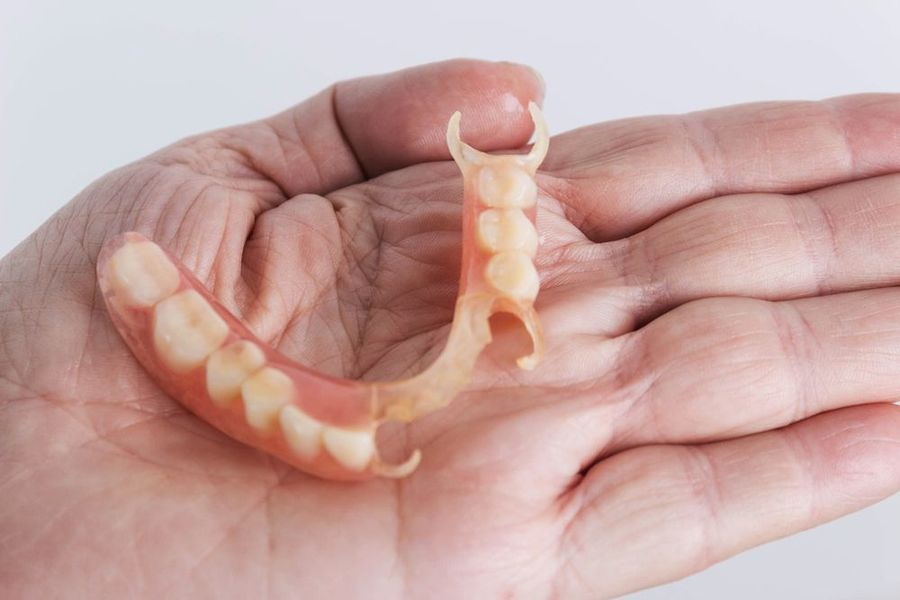 Person holding partial dentures in their hand