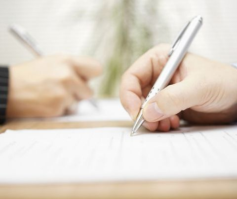Photo of a hand signing a document