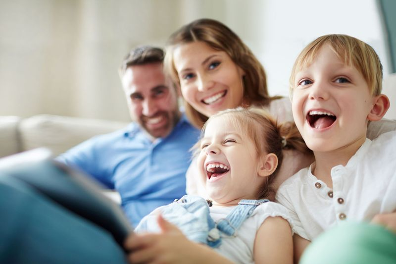 A smiling family reading a book together