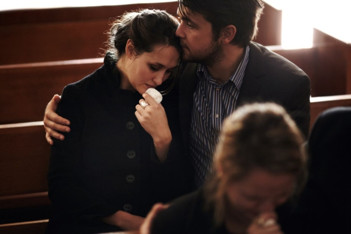 Man comforting woman during funeral