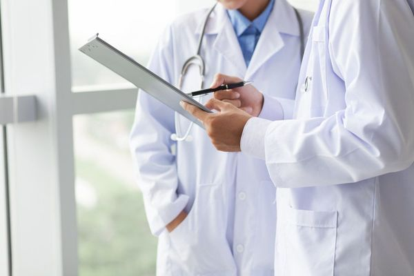 Two men in lab coats looking at a medical chart