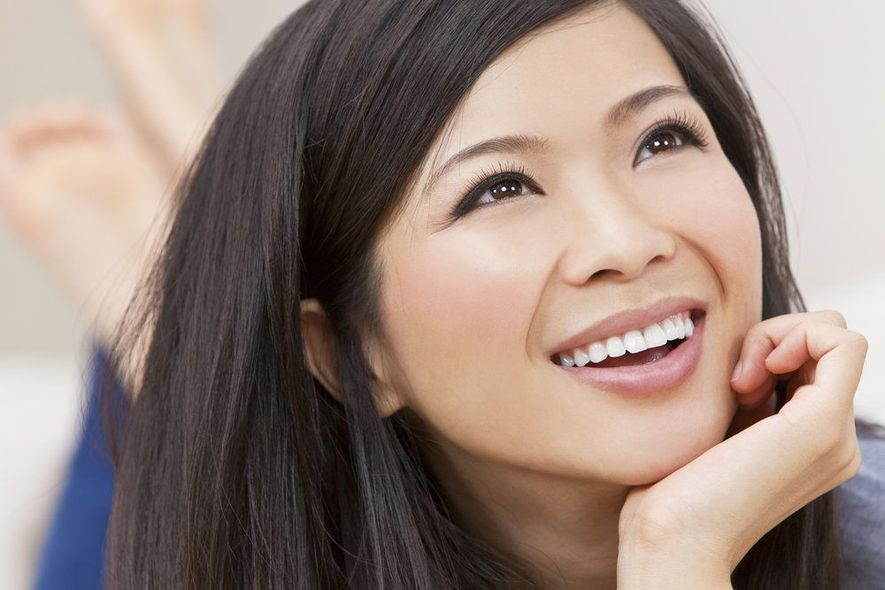 Smiling woman holding chin in hand