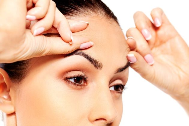 A woman touching her forehead and examining her eyebrows.