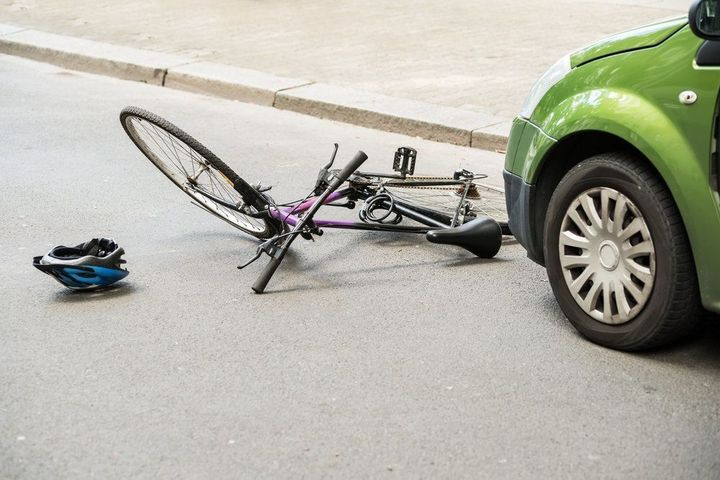 A bicycle lying in front of a car