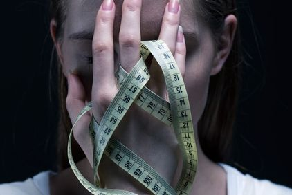 Distressed woman holding measuring tape over face