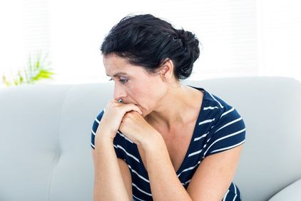 Distraught woman sitting on white couch