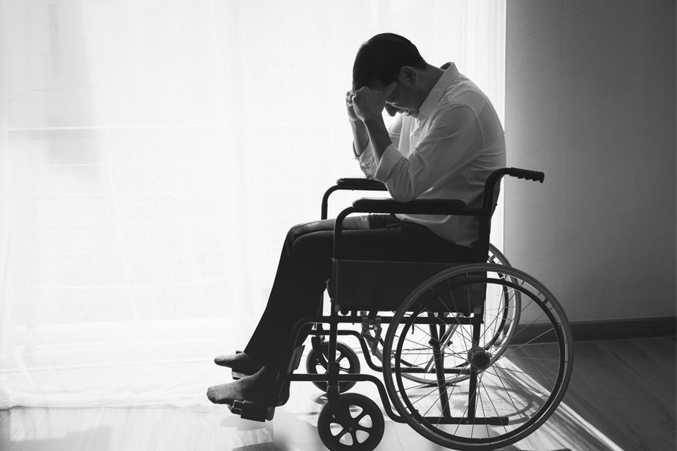 A man in a wheelchair with his head in his hands