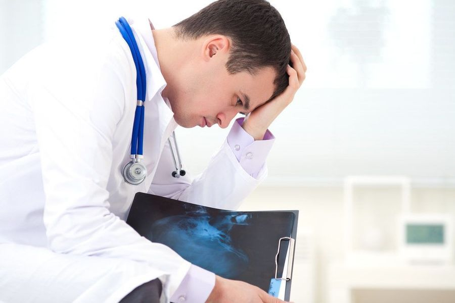Photo of a medical professional with head in hands