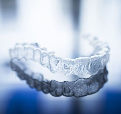 An Invisalign tray sitting on a shiny surface