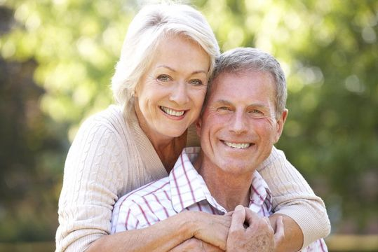 Older couple smiling together outdoors
