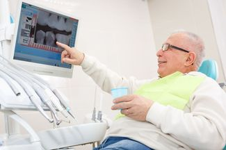 Man in dentist's chair pointing at x-rays