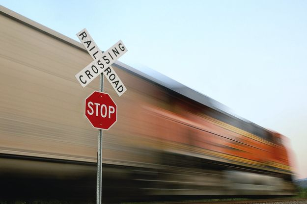 Railroad crossing sign in front of a passing train