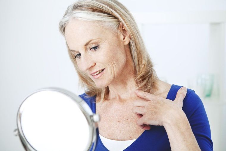 An older woman wearing a blue shirt looking at her neck in a mirror