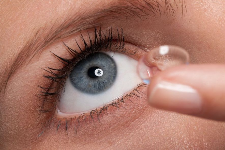 Close-up of a woman putting in a custom contact lens