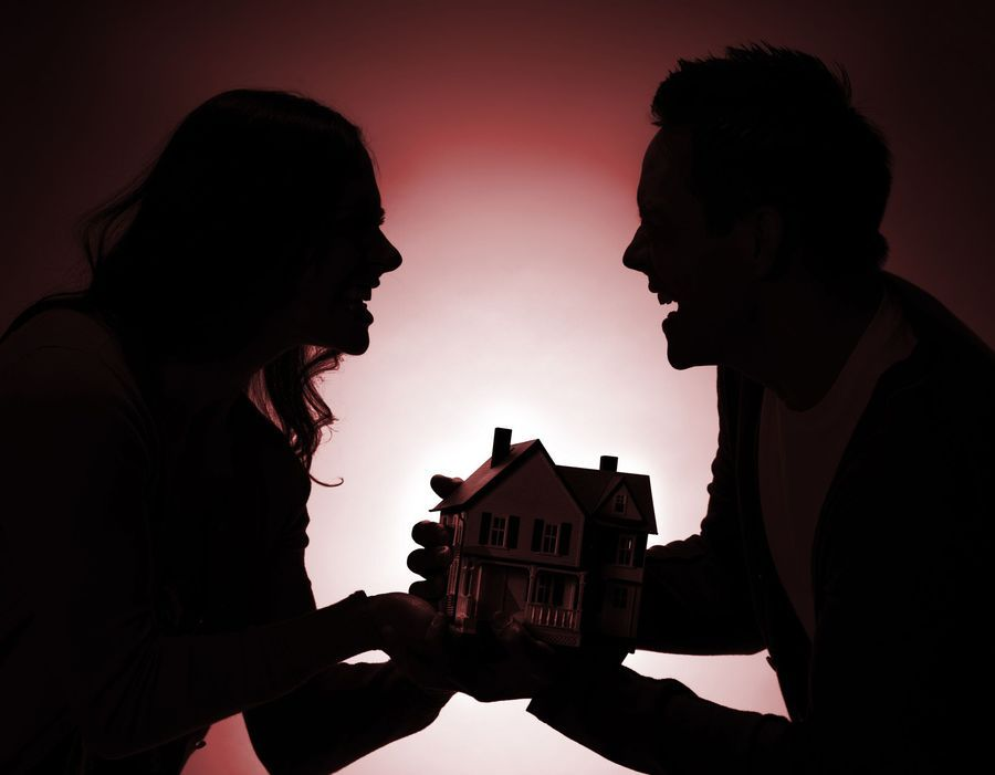 An image of a man and a woman in shadow fighting over a model house