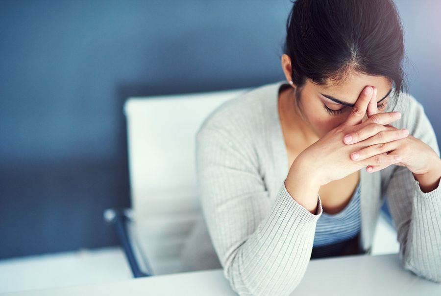 A frustrated woman sits at a desk