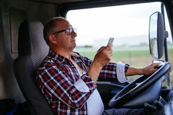 Truck driver texting on cellphone