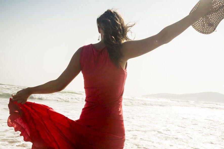 Woman on beach raising arms
