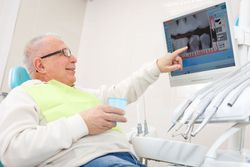 Older patient pointing to x-ray of teeth