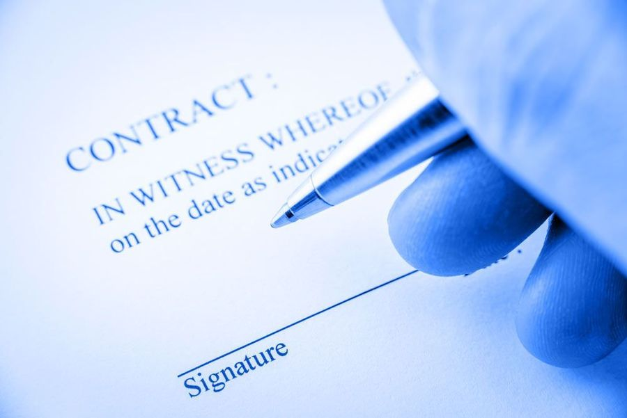 A hand holding a pen over a contract