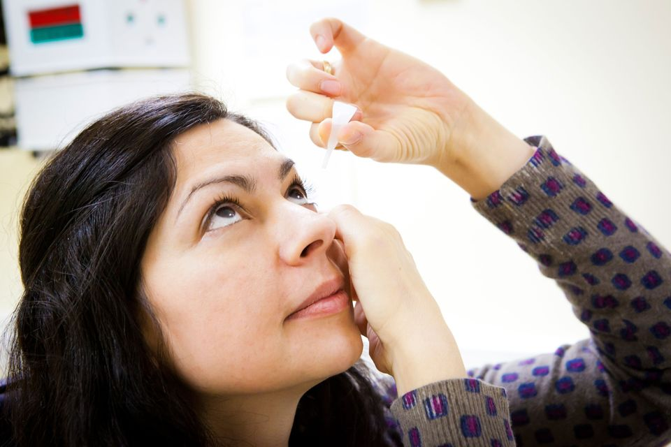 woman taking eye drops
