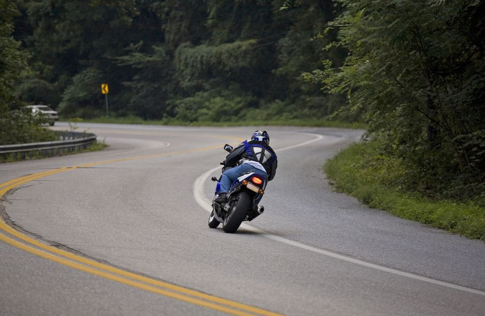 Motorcycle rider rounding bend in road