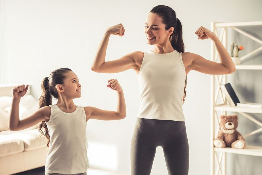 Mother and daughter flexing biceps together