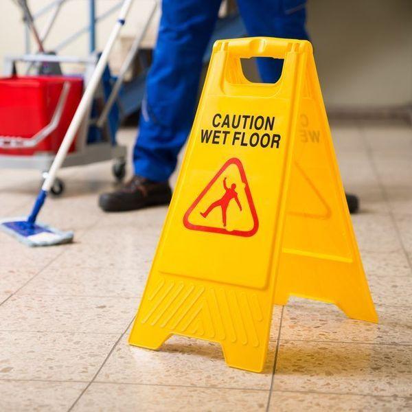 Yellow hazard sign on tile floor.