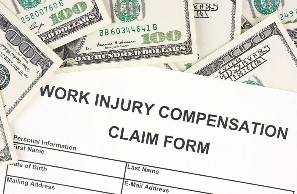 Dollar bills and a work injury compensation claim form.