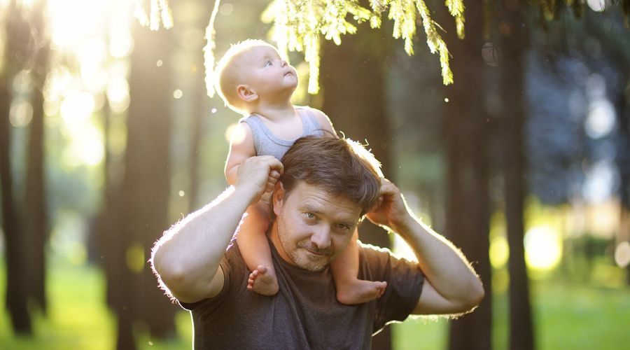 A man carries a young child on his shoulders
