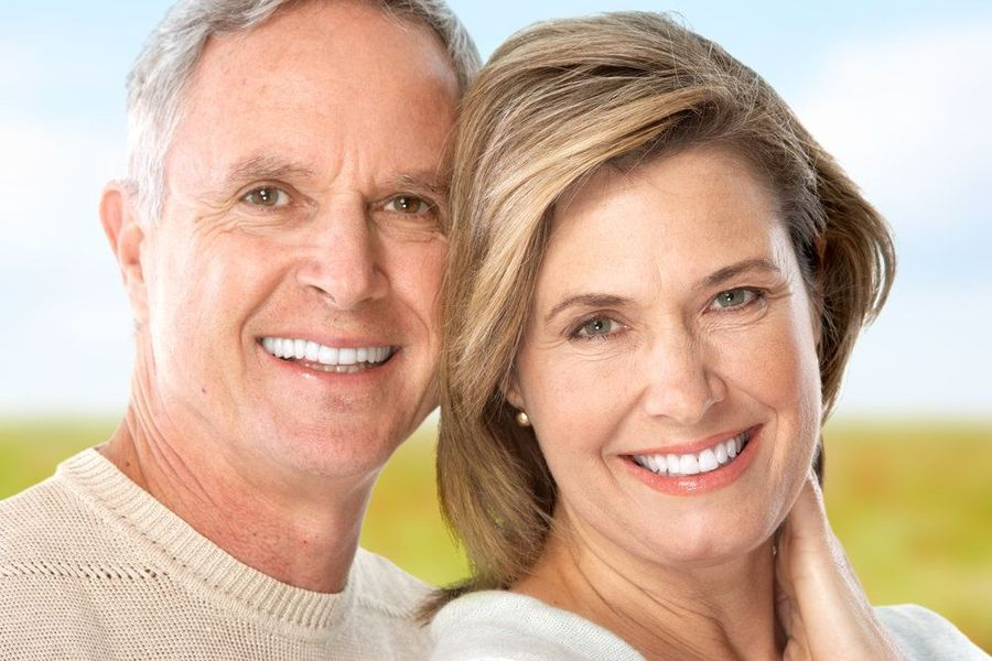 Older couple smiling with beige clothing