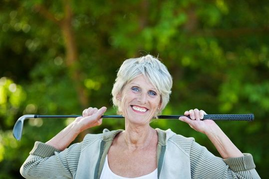 Smiling woman holding golf club over her shoulders
