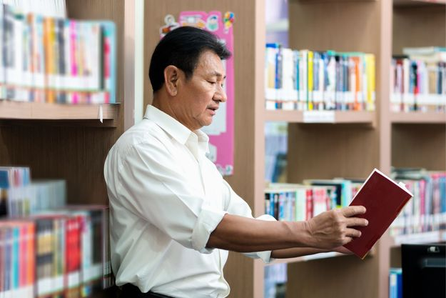 Man holding book away to see clearly