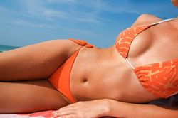 Woman in orange bikini reclining on the beach on her towel
