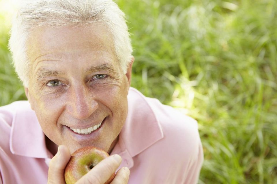 Older man smiling up into camera with apple in hand