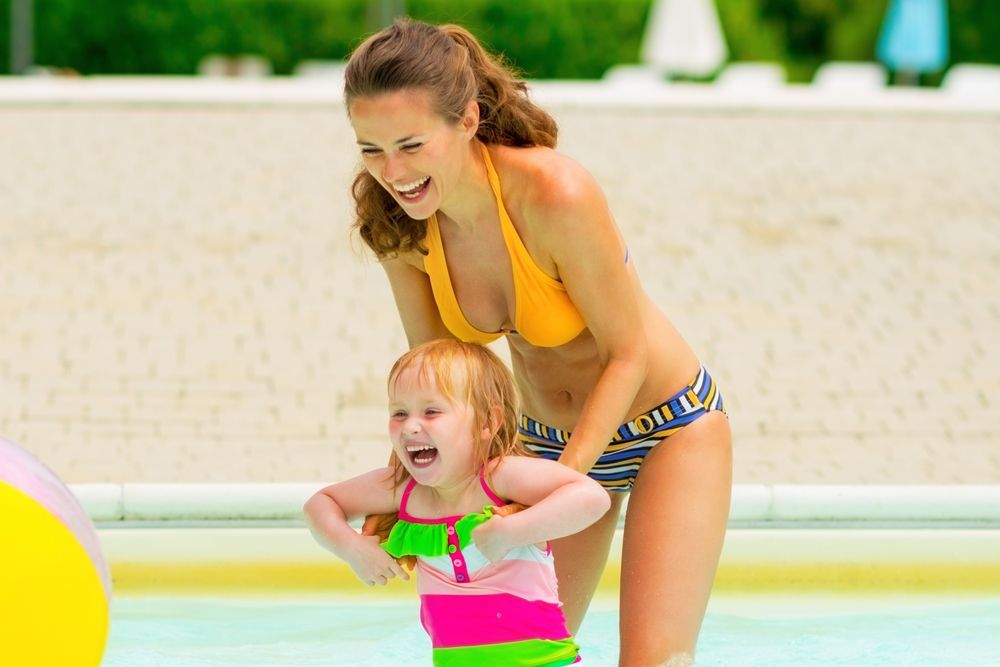 Young mother playing with daughter in pool