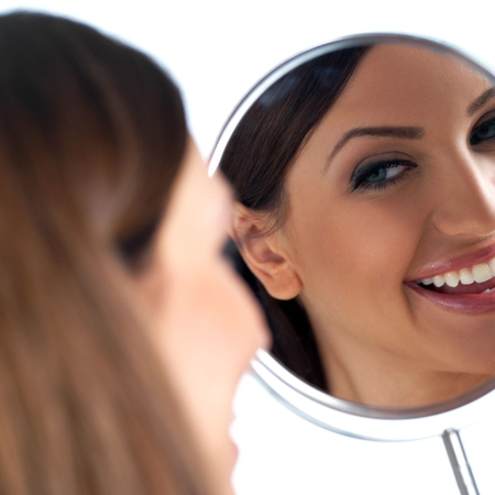 Woman smiling into mirror.